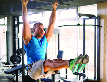 Sportsman doing abs workout on horizontal bar